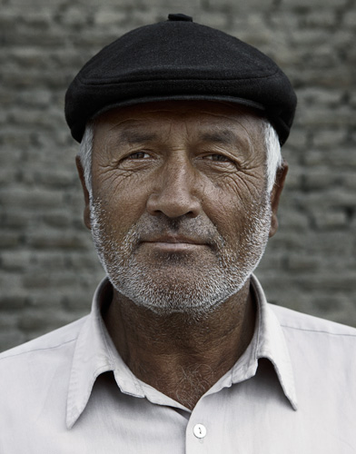 Afghan middle aged man with white beard wearing dark grey cap in Kabul portraits of afghanistan by photographer Kenneth Rimm